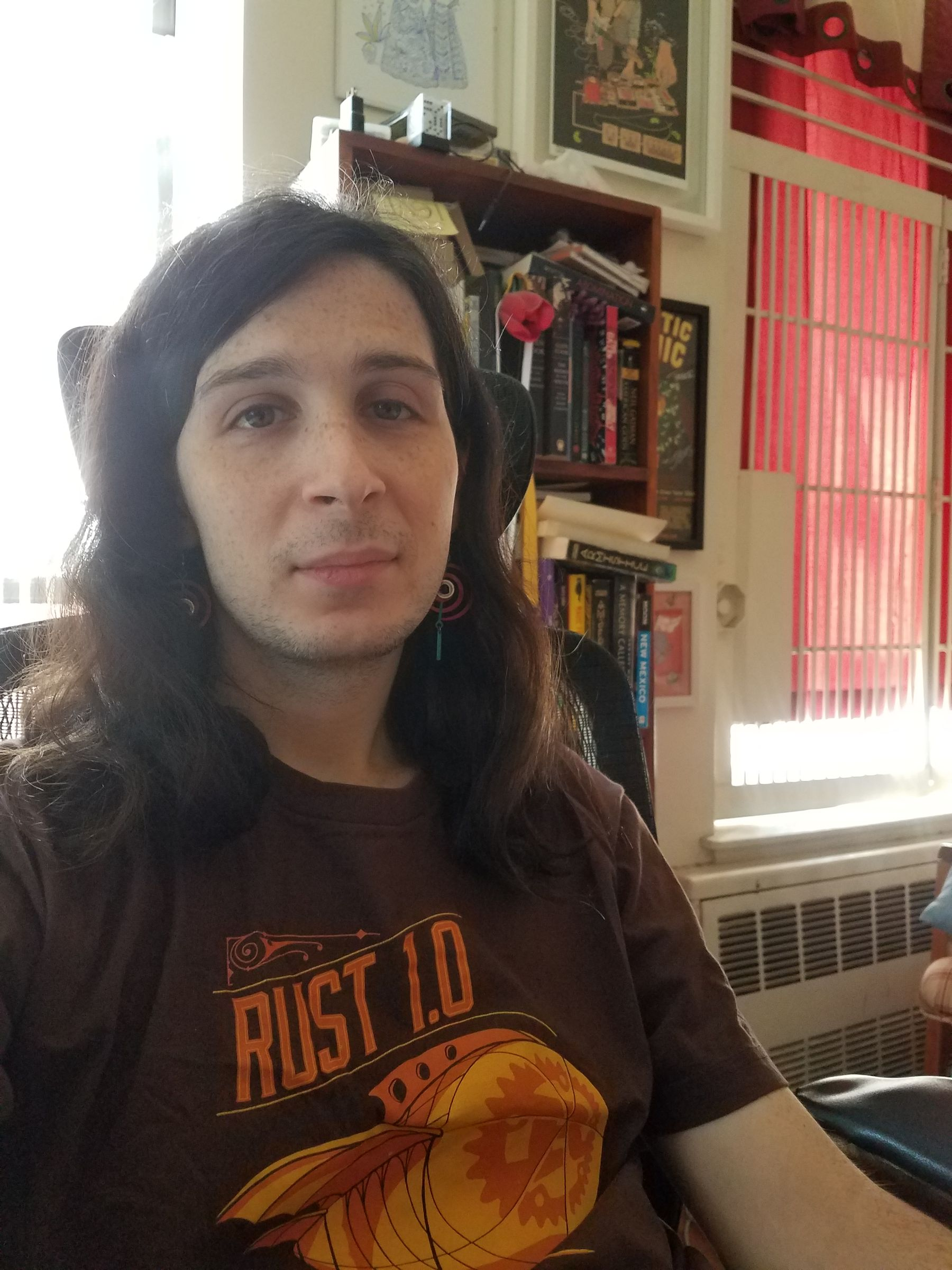 "Selfie of me, sitting indoors at a desk chair, wearing a brown ""Rust 1.0"" t-shirt. Behind me is a bookcase and two windows, one of which is filtering light through red drapes."