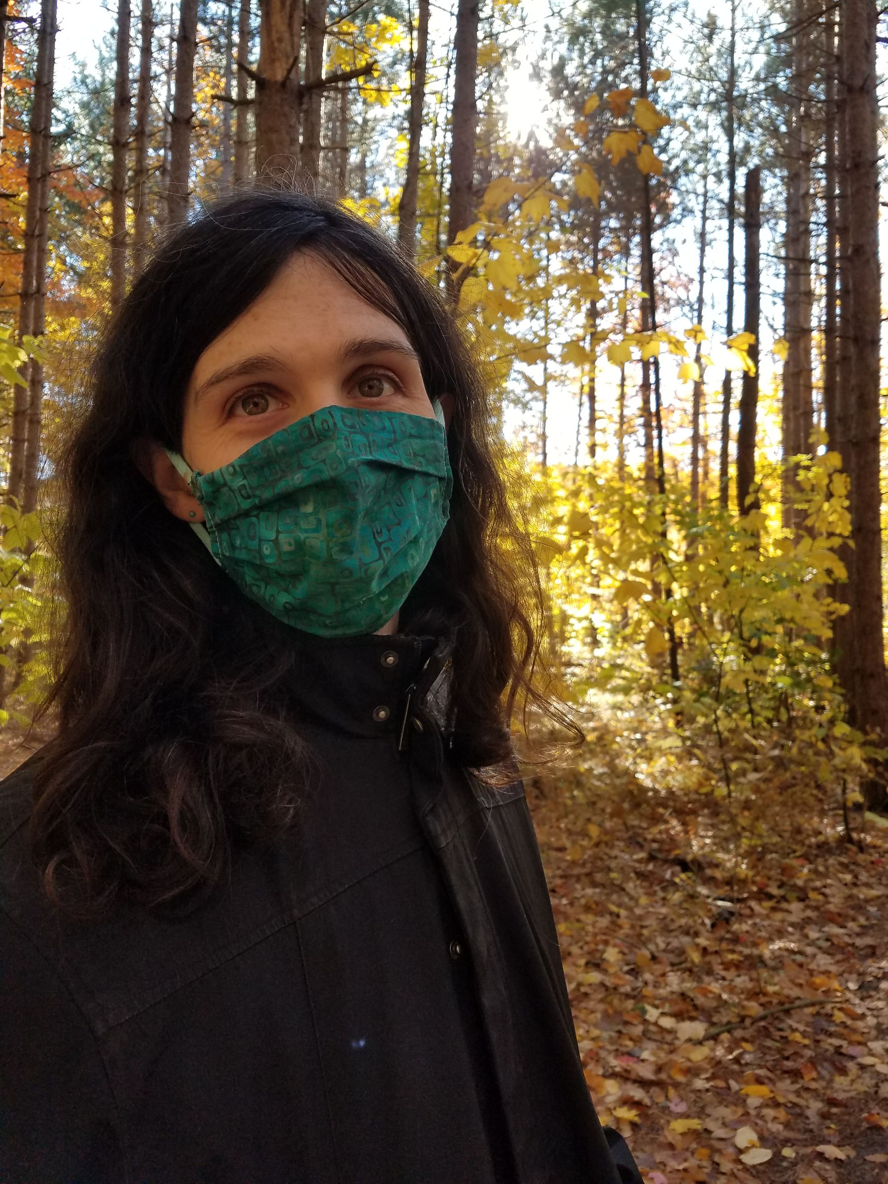Picture of me in a black coat and a teal mask, standing in the shade of the woods that's covered in orange foliage.
