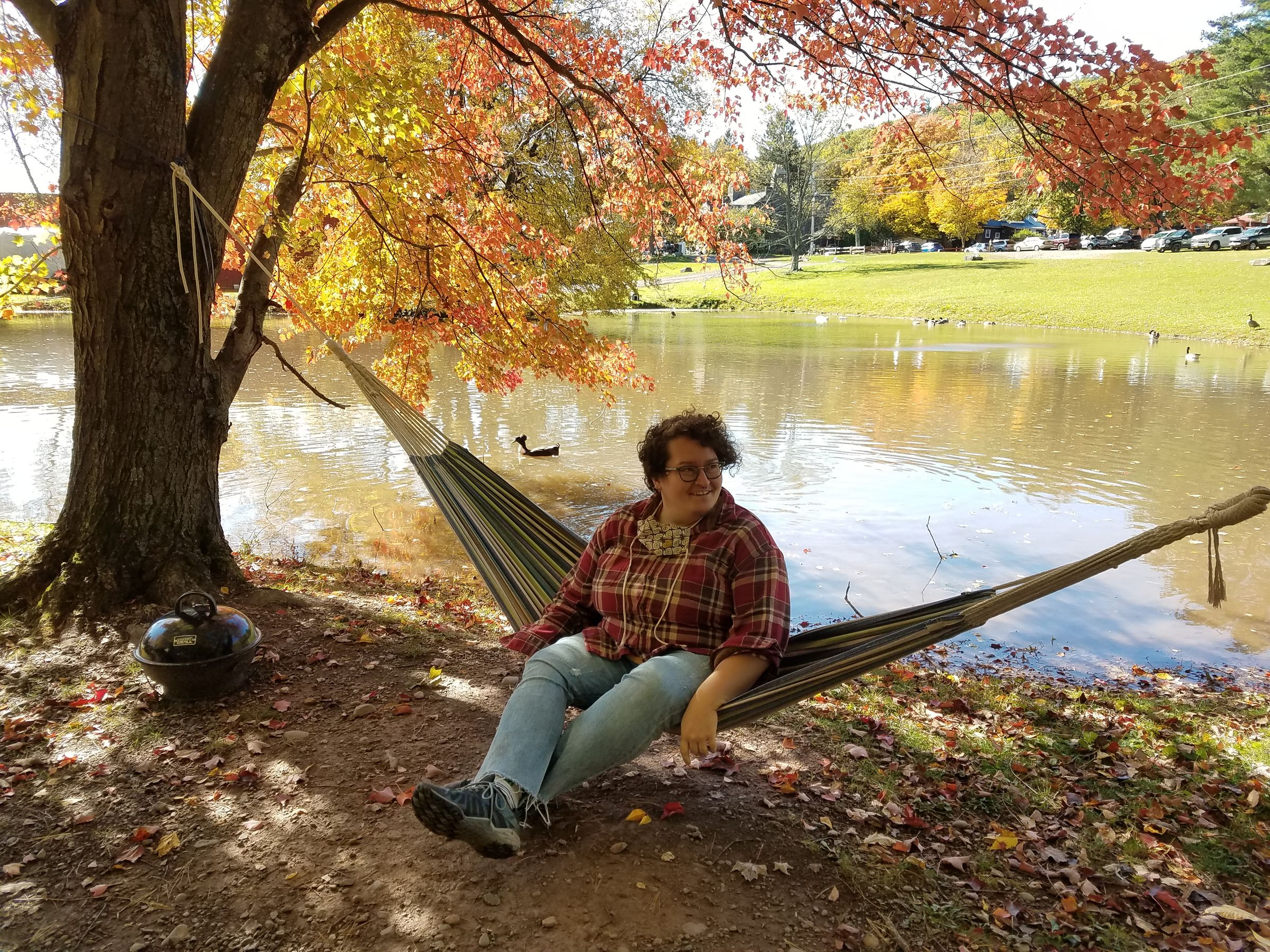 Photo of a person wearing jeans and a plaid flannel shirt, sitting on a hammock strung from two trees at the edge of a pond. The tree's leaves range from yellow to bright red. A few geese swim along the water's opposite bank.