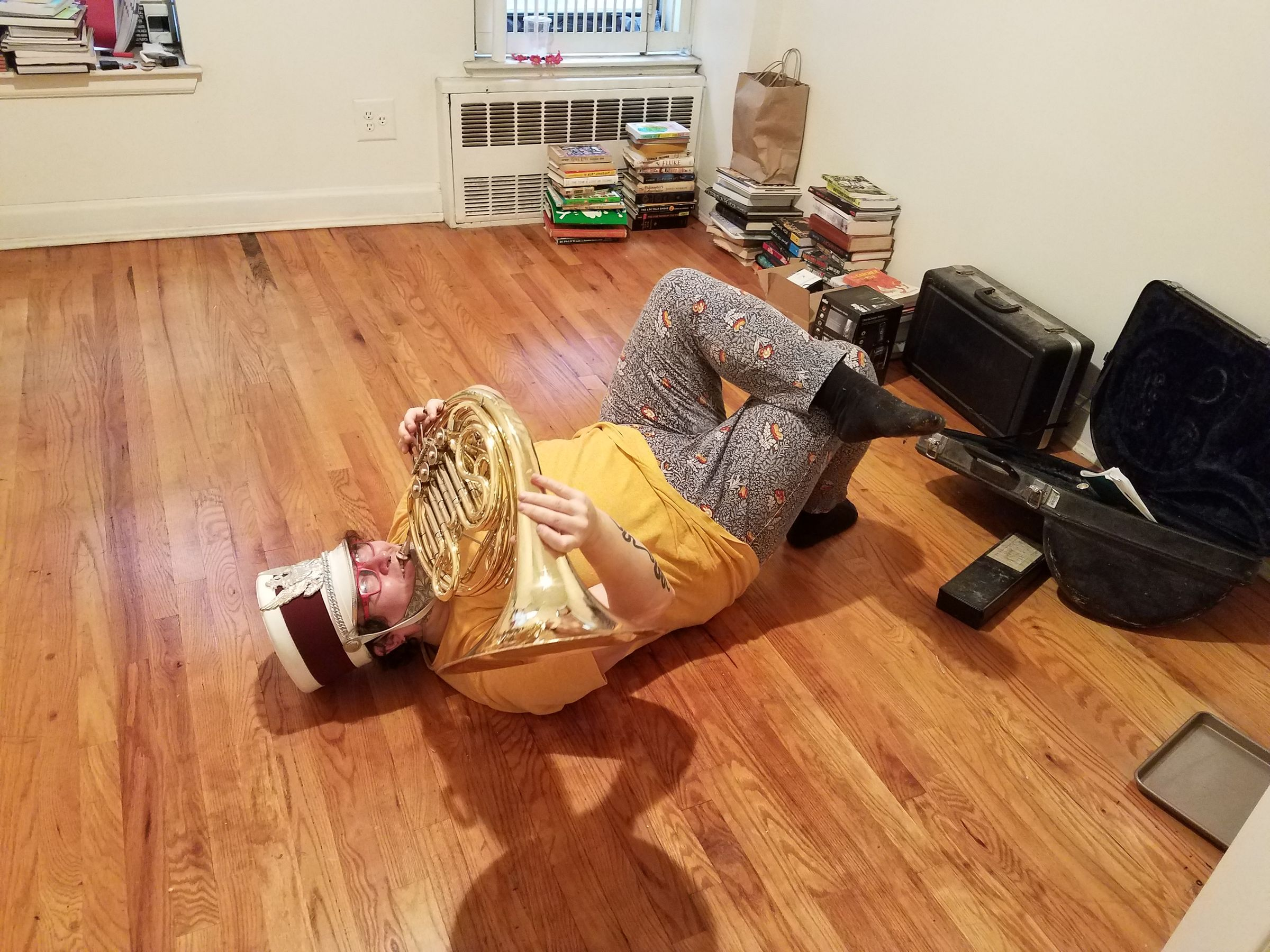 Photo of an empty apartment with stacks of books in the corner, and brass instrument cases against one wall. A person lies on the floor with their legs crossed, wearing a marching band hat, playing a French horn. They're also holding it wrong, with one hand trying to grab onto the outside of the bell.