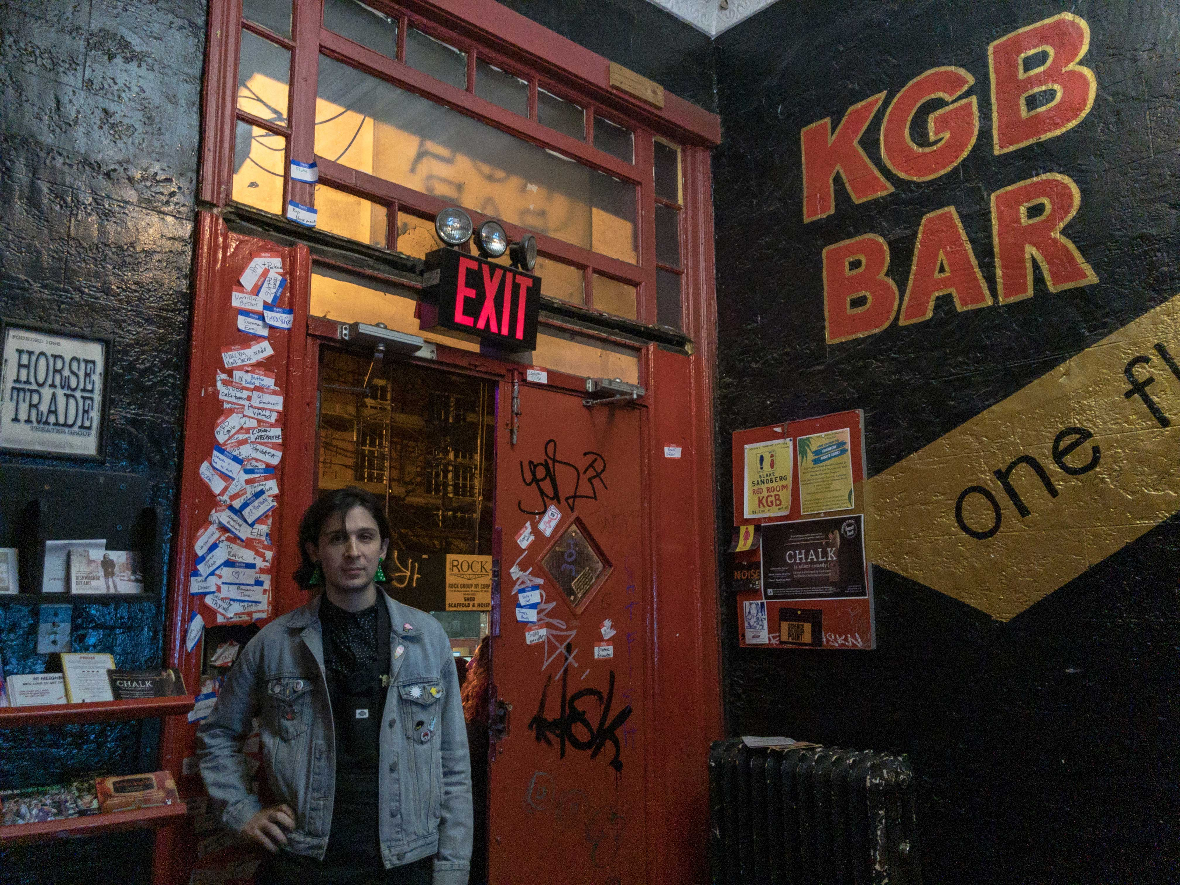 "The lobby of a building, painted black, facing the street exit. One wall is labeled ""KGB BAR"" in large red letters. The front door is bright red, with dozens of name tags stuck to the walls on either side. A person stands next to the exit with a hand on her hip, wearing a denim jacket."