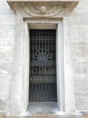 A dark metal barred door, recessed in white stone. In the center of the door is a circular seal with an hourglass and radiating spikes around it. Above the door is a stone carving of a pair of feathered wings.