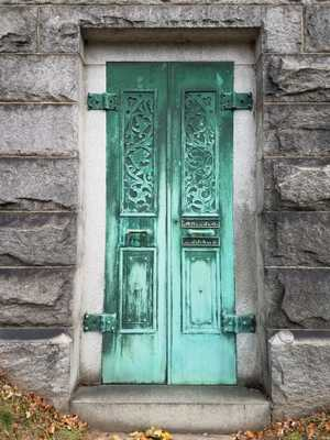 Double doors in rough hewn stone or cement brick walls. They are green with patina, and each have two decorated panels, with a handle in between.