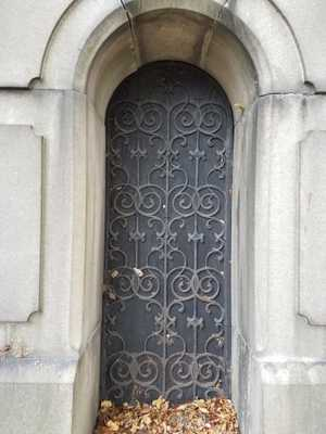 A close-up of a narrow wooden door with a circular top, covered in decorative wrought iron, and recessed into the wall of a mausoleum. Dead leaves collect in the doorway.