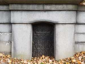 A squat mausoleum set into the side of a hill. It has a very small door with a shallow arched top, made of dark wood, with an elaborate wrought iron lattice laid over it. It has a long rectangular nameplate attached to the lattice.